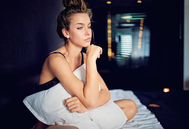 beautiful young girl with relationship difficulties standing sad in the bed - tragedy mask stock photos and pictures