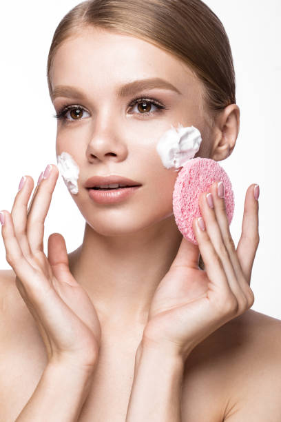 beautiful young girl with sponge and foam cleanser, french manicure - augen make up entferner stock-fotos und bilder