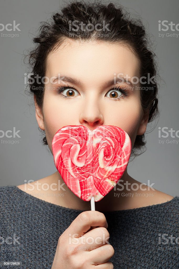 Beautiful young girl with tasty sweet lollipop stock photo