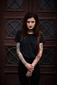 Tattooed young female model in black. Beautiful slim girl with black lips tattoos and piercing wearing casual  black clothes standing against wooden door. Alternative lifestyle