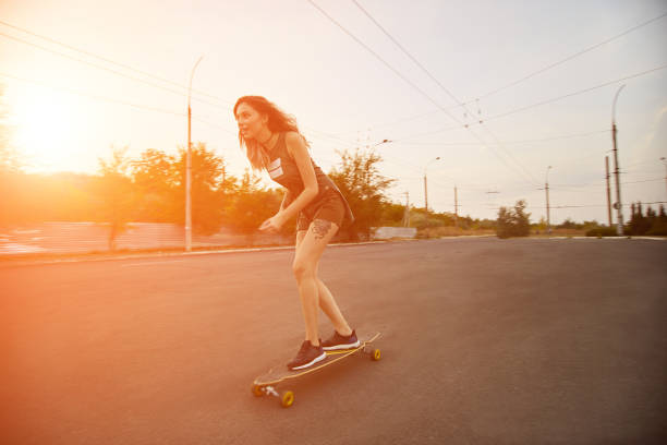 Beautiful young girl with tattoos riding longboard in sunny weather stock photo