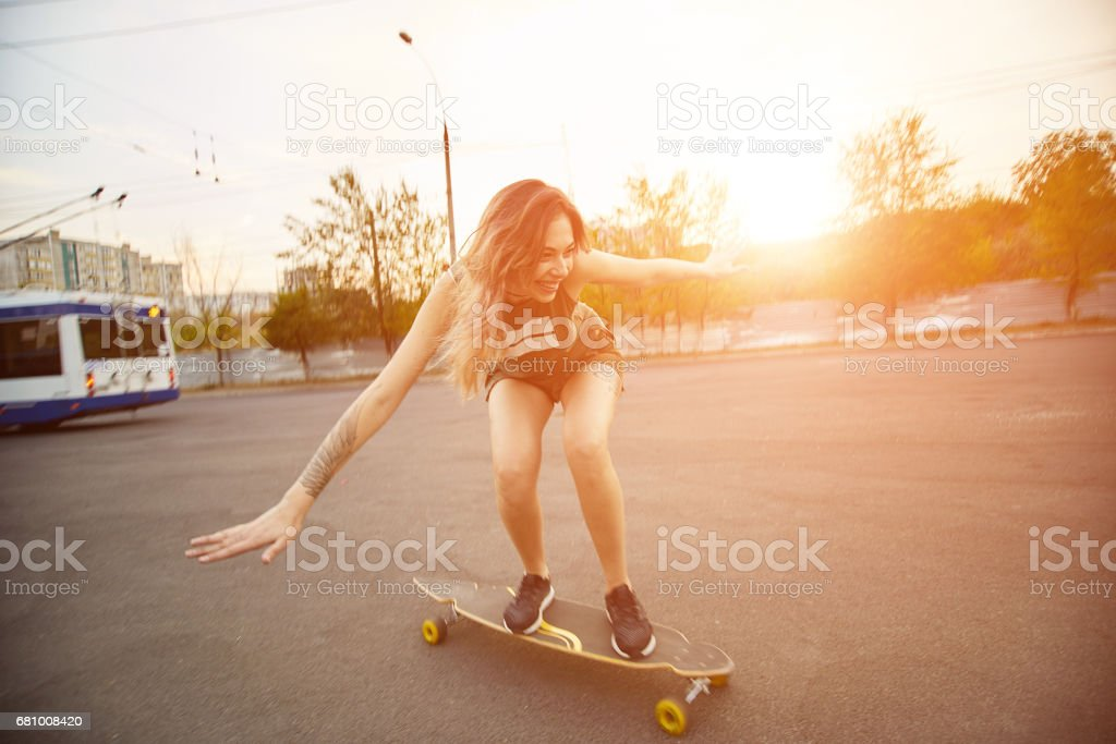 Beautiful young girl with tattoos riding longboard in sunny weather royalty-free stock photo