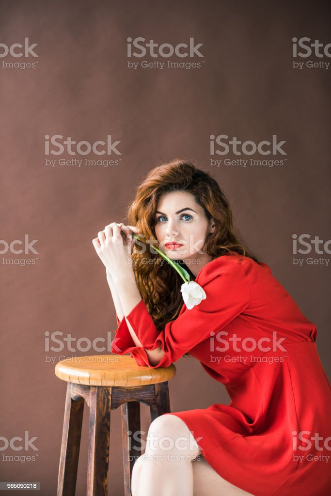Beautiful young girl with tulip flower leaning on stool isolated on brown background zbiór zdjęć royalty-free