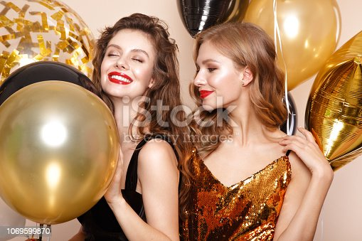 Beautiful young girls in elegant evening dresses with festive balloons. Beauty face. Photo taken in the studio