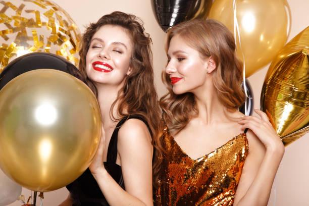 schöne junge mädchen in eleganten abendkleidern mit festlichen ballons. beauty gesicht. - kleid mit verzierung stock-fotos und bilder