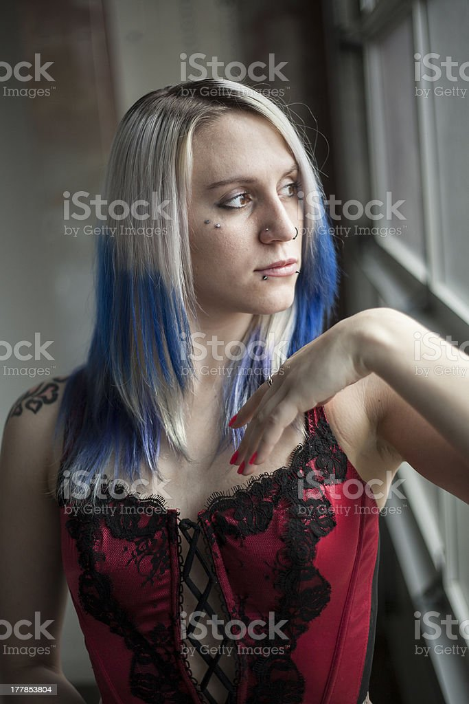Beautiful Young Goth Woman with Blue Hair and Red Corset stock photo