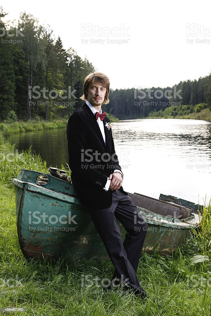 Beautiful young groom sitting on boat royalty-free stock photo