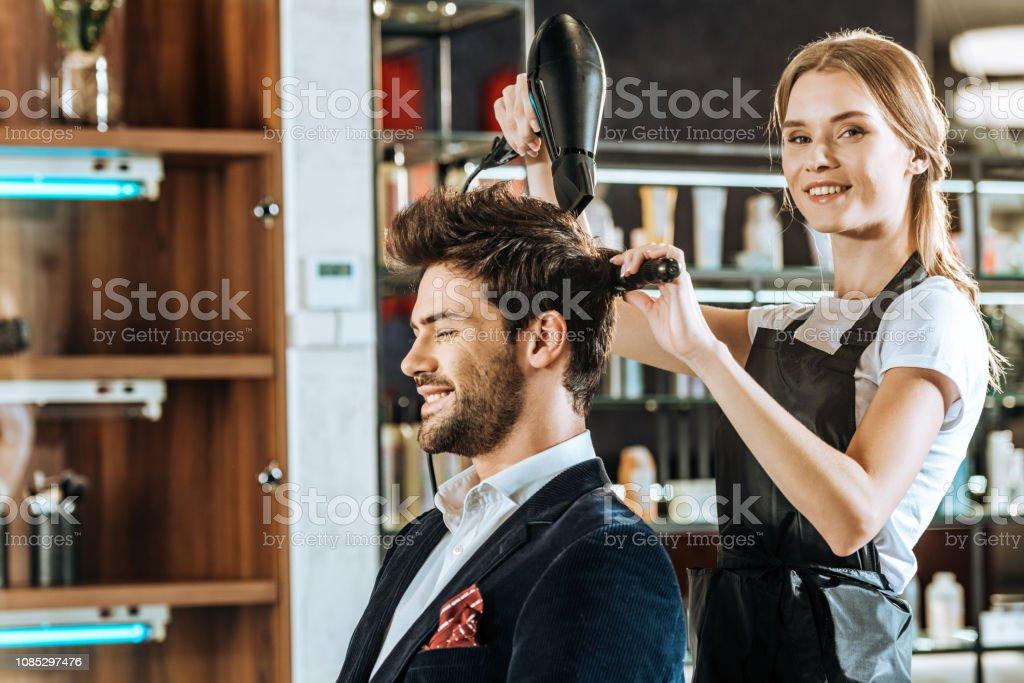 美麗的年輕髮型師微笑著在相機, 而乾燥和梳理頭髮英俊的客戶在美容院 - 免版稅人圖庫照片