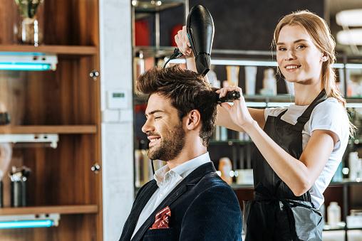 美麗的年輕髮型師微笑著在相機 而乾燥和梳理頭髮英俊的客戶在美容院 照片檔及更多 人 照片