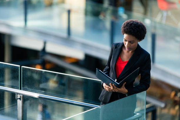Beautiful young Haitian businesswoman standing on balcony A beautiful young haitian businesswoman standing on a balcony, holding a file and looking at it. haitian ethnicity stock pictures, royalty-free photos & images