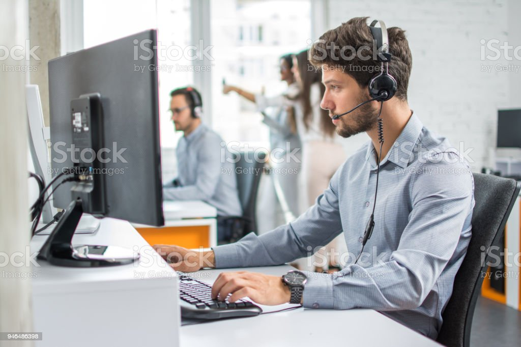 Beautiful young handsome customer support operator with hands-free set working on computer in call centre stock photo