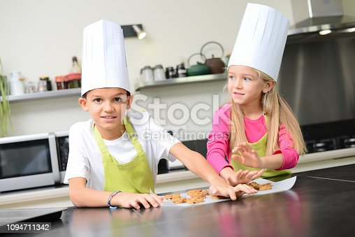 istock beautiful young happy kids boy and girl cooking and baking a cake in kitchen at home 1094711342