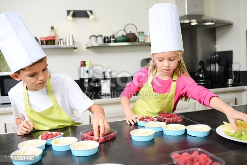 istock beautiful young happy kids boy and girl cooking and baking a cake in kitchen at home 1124283490