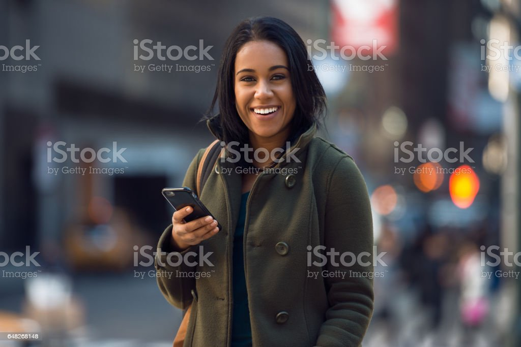 Beautiful young happy latin woman texting on mobile phone stock photo