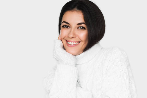 Beautiful young happy woman looking pensive and happy in white sweater on light grey background. Pretty brunette with healthy teeth smile woman studio portrait. Positive mood. stock photo