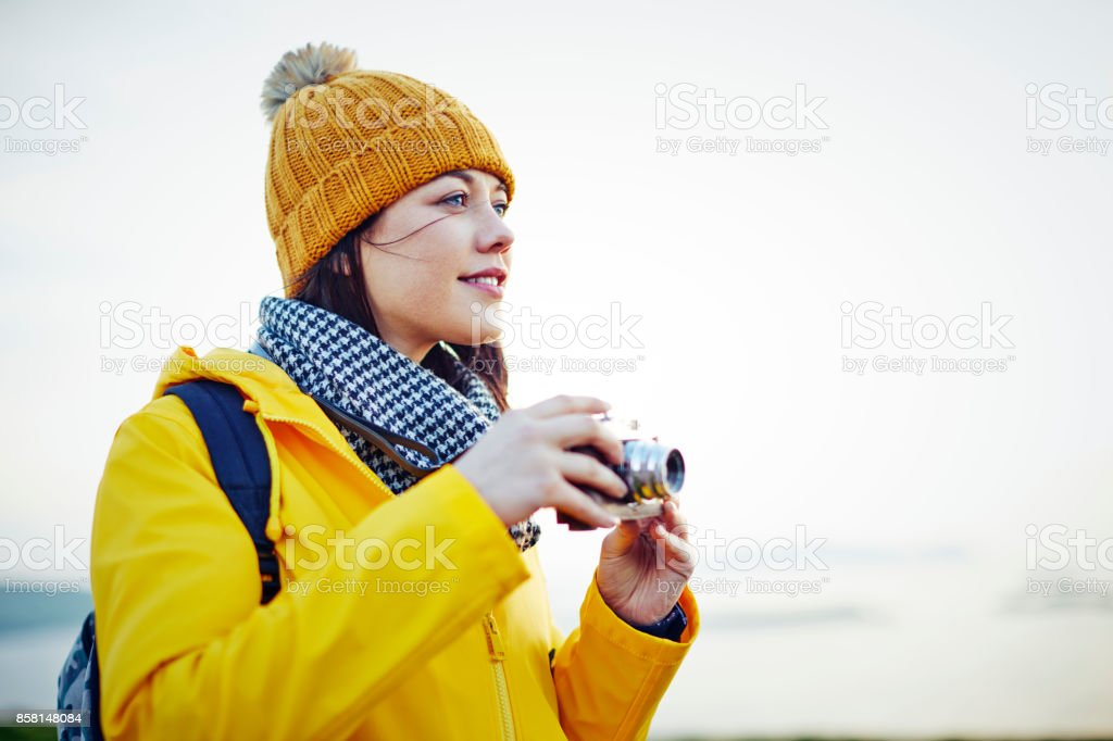 Beautiful young hiker holding vintage camera against clear sky stock photo