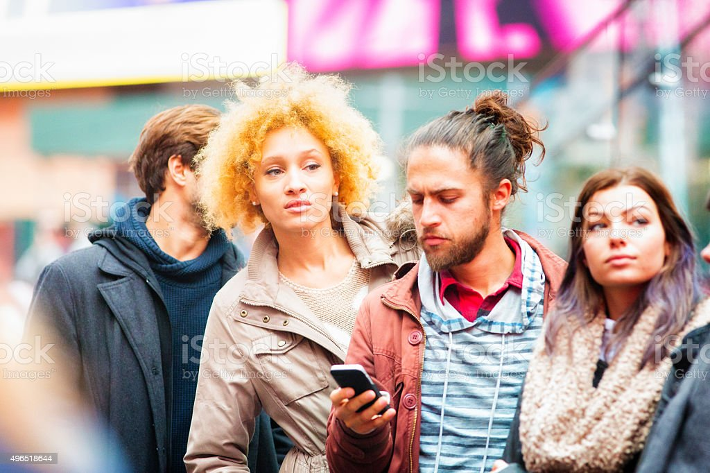 Beautiful young hip mixed-race woman getting impatient in line stock photo