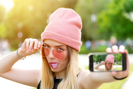 Beautiful young hipster girl makes self portrait on smartphone view of screen