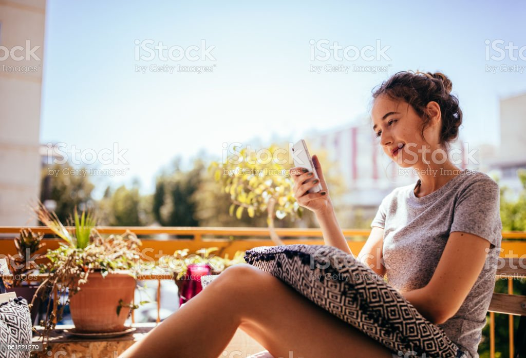 Beautiful young hipster woman sitting on balcony using smartphone stock photo