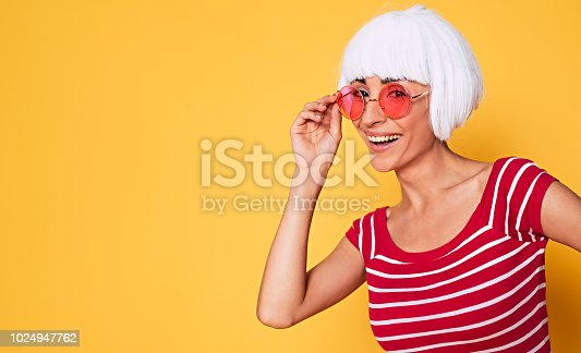 483075616 istock photo Beautiful young hipster woman wearing blonde wig and pink sunglasses posing against orange background 1024947762