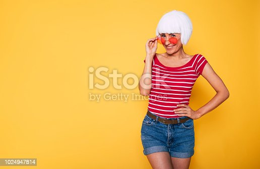 483075616 istock photo Beautiful young hipster woman wearing blonde wig and pink sunglasses posing against orange background 1024947814