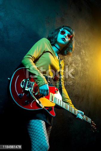 Beautiful young hipster woman with curly hair with red guitar in neon lights. Rock musician is playing electrical guitar. 90s style concept