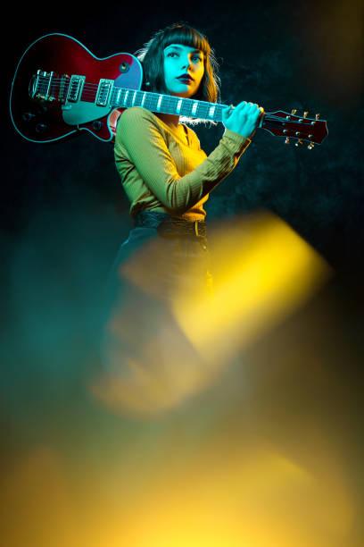schöne junge hipster-frau mit lockigen haaren mit roter gitarre in neonlicht. rockmusiker spielt elektrische gitarre. 90er-jahre-konzept. - bands der 90er stock-fotos und bilder