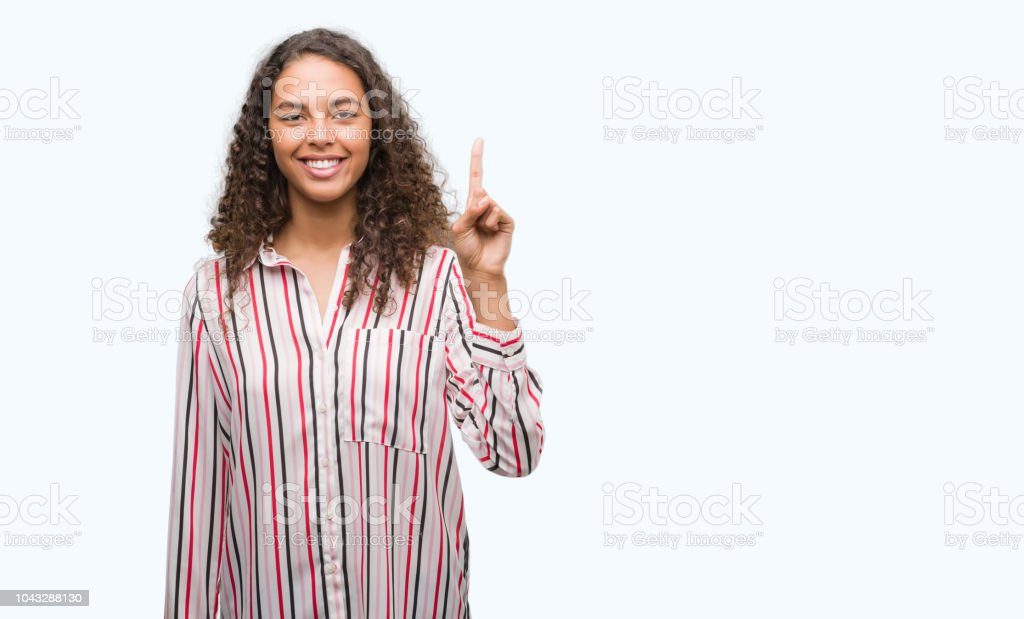 Beautiful young hispanic woman showing and pointing up with finger number one while smiling confident and happy. stock photo