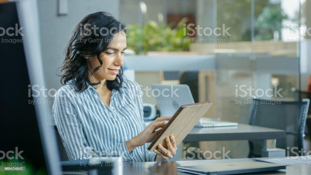 아름 다운 젊은 히스패닉 여자는 그녀의 책상을 사용 하 여 태블릿 컴퓨터에 앉는 다. 일 하는 동료와 함께 배경 바쁜 사무실. - 로열티 프리 갈색 머리 스톡 사진