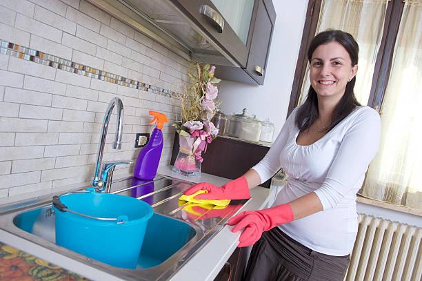 Schöne junge Hausfrau Reinigung der Möbel in der Küche – Foto