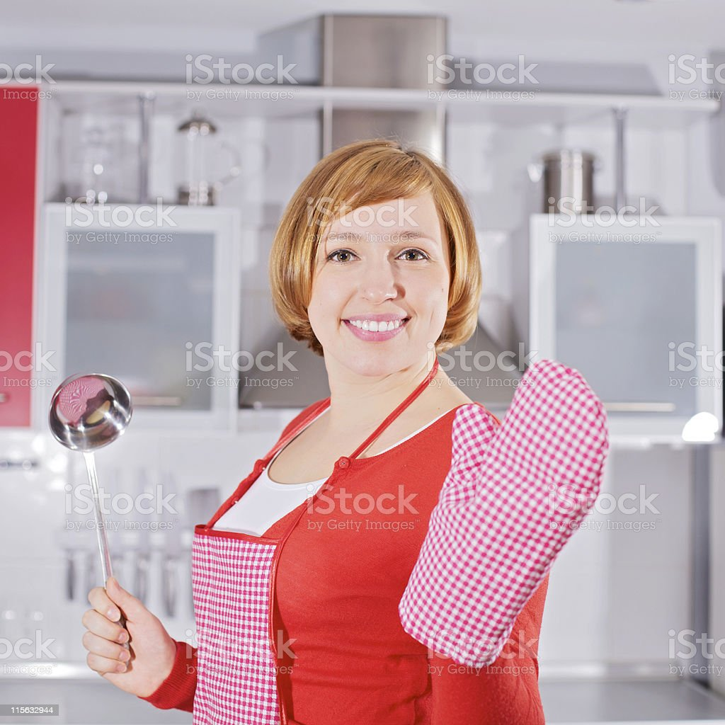 Beautiful young housewife in kitchen holding ladle stock photo
