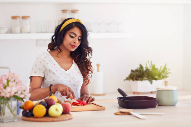 beautiful young indian woman cutting vegetables on the kitchen, healthy eating stock photo