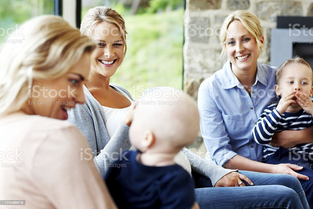 Beautiful young ladies with their kids sitting together stock photo