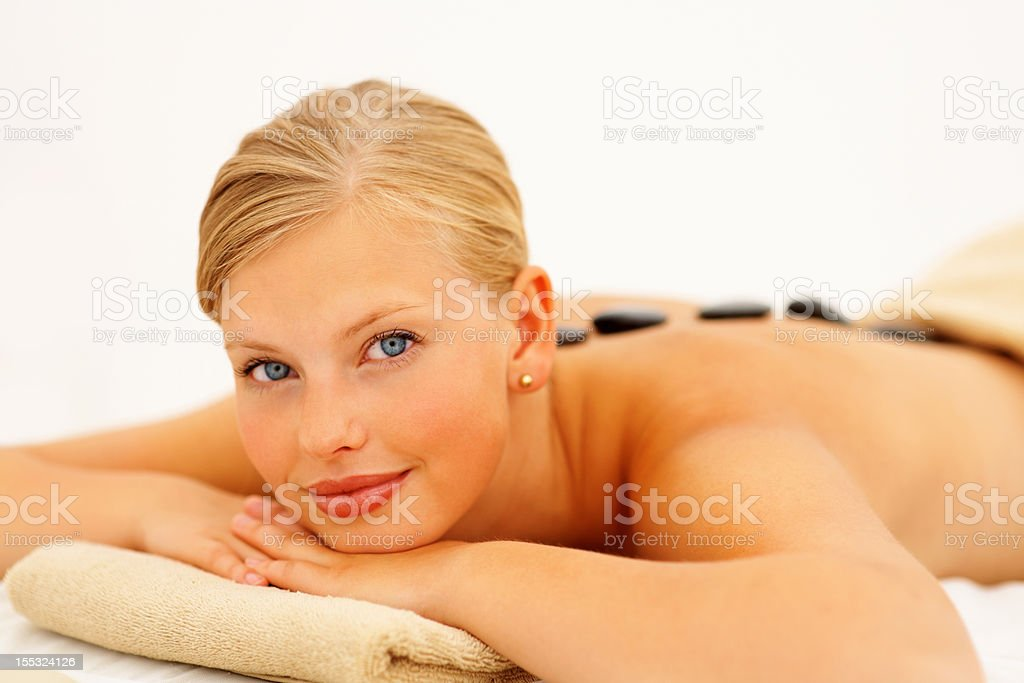 Beautiful young lady receiving hot stone therapy royalty-free stock photo
