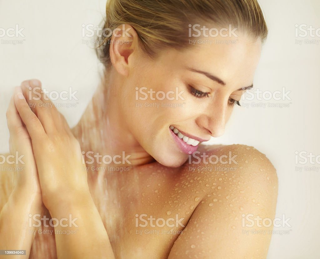 Beautiful young lady taking a bath under shower stock photo
