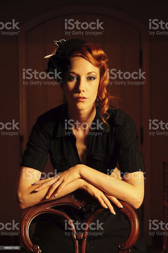 Beautiful young lady with curly red hair in rich decor royalty-free stock photo