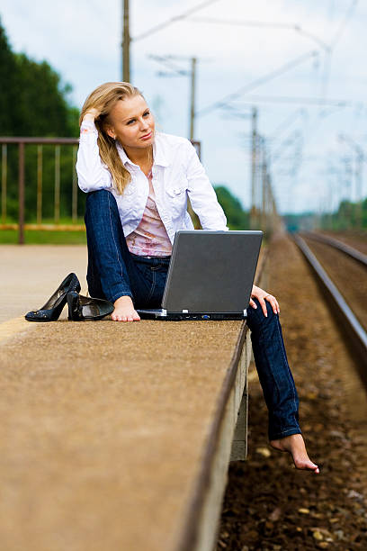 beautiful young lady with notebook waiting a train stock photo