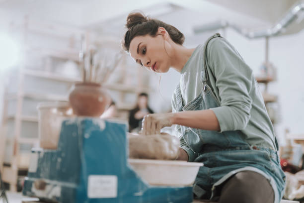 beautiful young lady working on pottery wheel - garncarz zdjęcia i obrazy z banku zdjęć