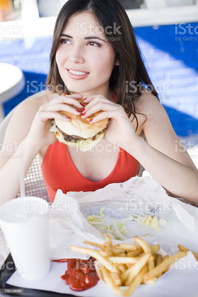 beautiful young latin girl eating fast food royalty-free stock photo