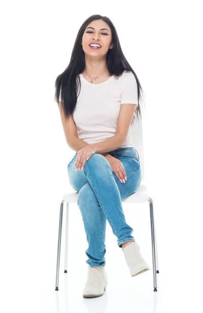 Schöne junge Latino-Hündin mit einem T-Shirt und Jeans-sitzen – Foto