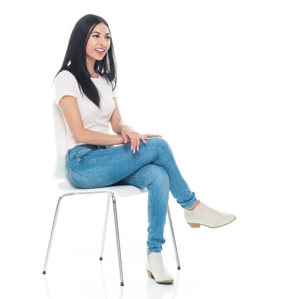 Beautiful young latino female wearing a tshirt and jeans - sitting Beautiful young latino female wearing a tshirt and jeans - sitting sitting stock pictures, royalty-free photos & images