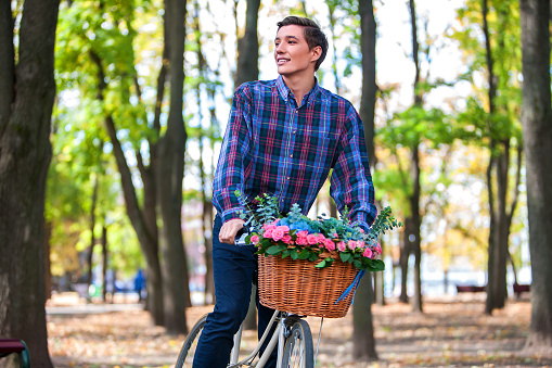 Beautiful young man on bike in park