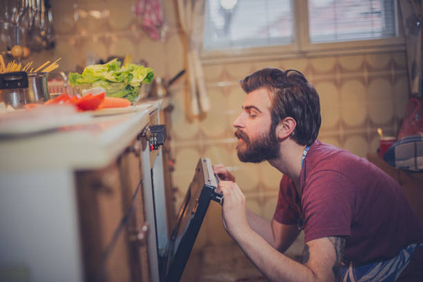 Beautiful young man preparing healthy meal Beautiful young man preparing healthy meal oven stock pictures, royalty-free photos & images