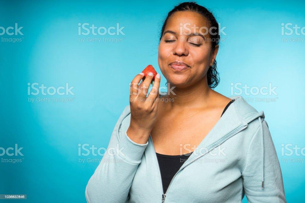 캐주얼 의류 먹고 하 고 파란색 배경으로 신선한 딸기를 즐기는 여 자가 아름 다운 젊은 혼합된 인종 - 로열티 프리 건강한 생활방식 스톡 사진