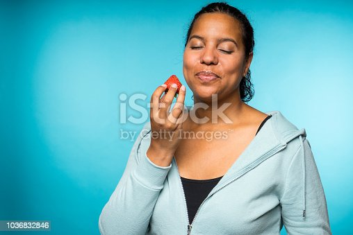 Beautiful young mixed race woman in casual clothing eating and enjoying a fresh strawberry with a blue background