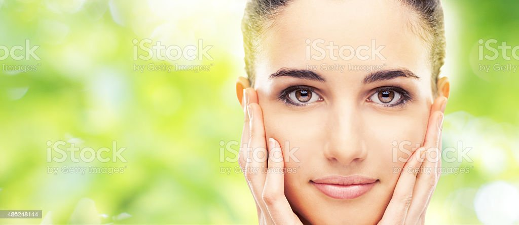Beautiful young model touching her skin stock photo