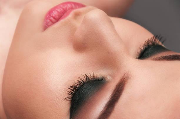 beautiful young model with professional make up, close up shot on the grey background - vlad models стоковые фото и изображения