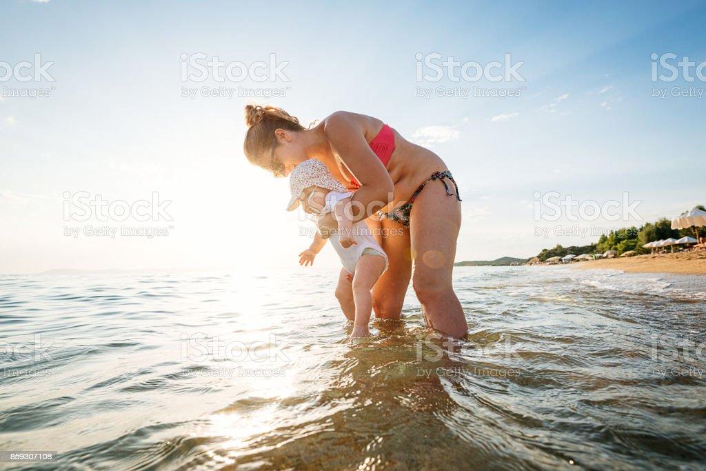 Schöne junge Mutter und ihre kleine Tochter schwimmen lernen Lizenzfreies stock-foto