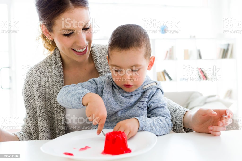 Beautiful young mother and her son eating strawberry jelly at home. stock photo