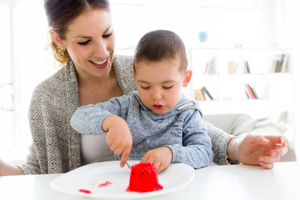 Beautiful young mother and her son eating strawberry jelly at home. Portrait of beautiful young mother and her son eating strawberry jelly at home. gelatin stock pictures, royalty-free photos & images
